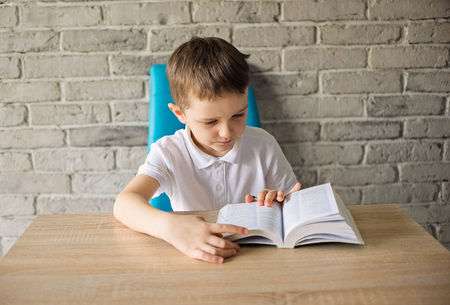 6 year old: 6 year old boy in a white polo shirt reading a book at the table