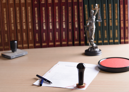 signed: Signed by a notary public document with his stamp and pen. Themis with scales of justice in the background Stock Photo
