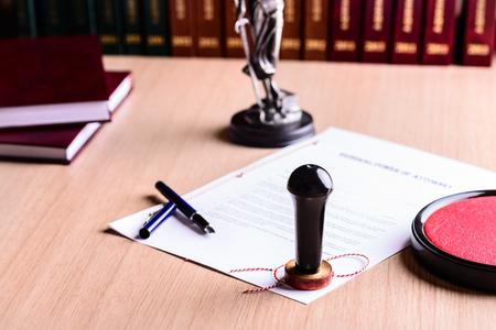 Pieczęć notariusza na podpisanego pełnomocnictwa. Pióro i Temida z wagą sprawiedliwości w tle.