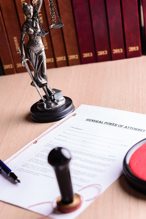 certifying: Notary public stamp on signed power of attorney. Pen and Themis with scales of justice in the background. Stock Photo