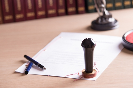 acts: Stamp of the notary on testament and last will. In the background notarial acts