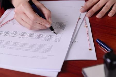 Gros plan d'une main signature atestament par un stylo.