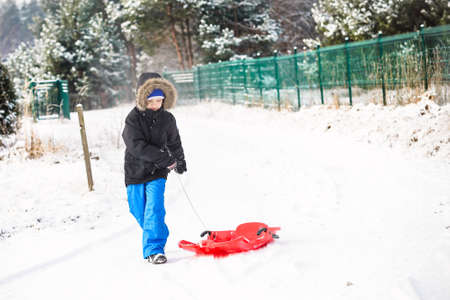 country boy: Child pulling red plastic sled. Winter fun Stock Photo