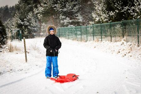 6 years: 6 years boy pulls his red plastic sled. Winter fun Stock Photo