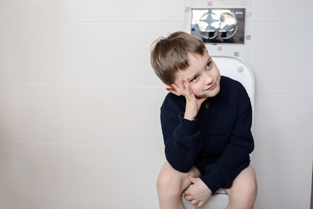 6 year old: Thinking 6 year old boy sitting on the toilet. Dressed in a dark navy blue woolen sweater Stock Photo