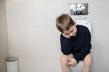 화장실에 앉아 사려 깊은 6 살짜리 아이 스톡 콘텐츠