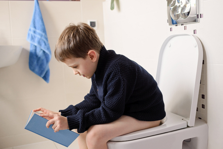 Little 6 year old boy sitting on the toilet and reading a blue book