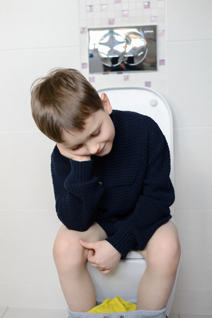 Thoughtful 6 year old boy sitting on the toilet Stock Photo