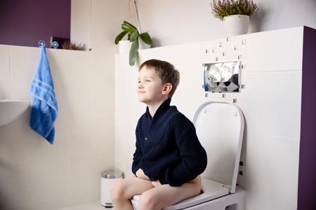 inodoro: Feliz sonriente muchacho de 6 años que se sienta en el inodoro. Vestido con un suéter azul marino oscuro de lana Foto de archivo
