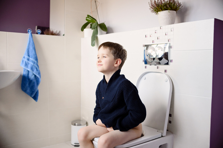 Sourire heureux garçon de 6 ans assis sur les toilettes. Vêtu d'un bleu marine laine chandail bleu Banque d'images