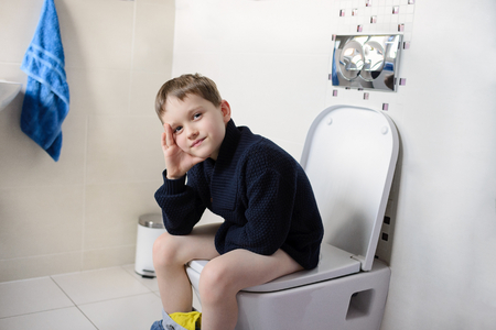 pis: niño reflexivo sentado en el inodoro. Vestido con un suéter azul marino oscuro de lana