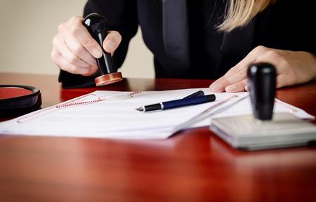 Zbliżenie na ręce notarialne za stemplowania dokumentu. Notariusz akcesoria publiczne