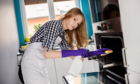 A young woman cleans the oven. Rubber gloves on her hands. Using cleaning fluid and sponge. Dressed in a plaid shirt and white apron