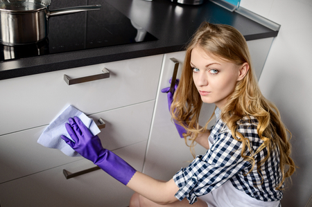 kitchen cabinets: A young woman cleans the kitchen cabinets. Rubber gloves on her hands. For cleaning using cleaning fluid and cloth Stock Photo