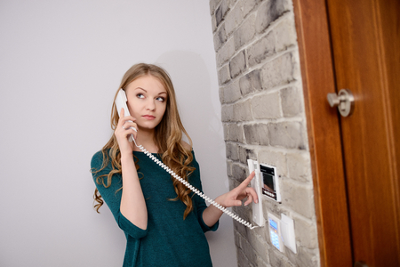 interphone: Blonde woman talking on the intercom and presses the button to open the door