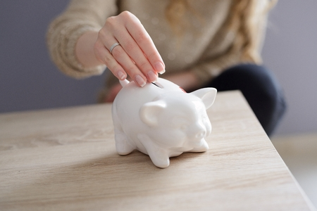 white piggy bank: Closeup of a womans hand inserting a coin into piggy bank