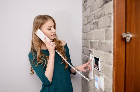여자가 인터콤에서 이야기하고 문을 열기 위해 버튼을 누르십시오. 스톡 콘텐츠