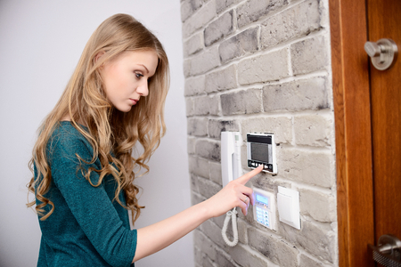 desired: The woman sets the desired temperature in home heating system