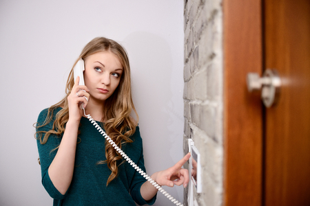 interphone: Young blonde woman talking on the intercom and presses the button to open the door