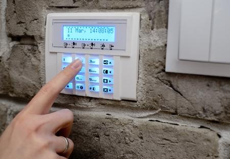 Close-up op de vrouw vinger invoeren van code in het toetsenbord van het alarmsysteem en activeert het alarm