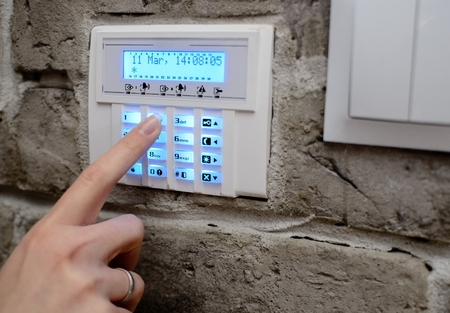 Closeup on woman's finger entering code into the keypad of the alarm system and activates the alarm