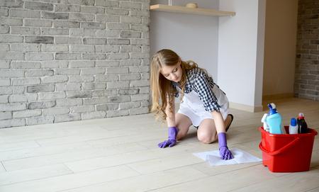 mujer limpiando: La mujer lava el suelo en la habitación de rodillas. Vestido con un delantal blanco y una camisa a cuadros. guantes de goma protectores en sus manos Foto de archivo