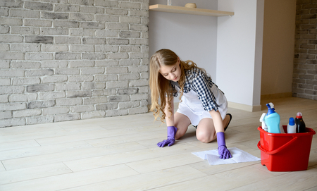 Woman washes the floor in the room on her knees. Dressed in a white apron and a plaid shirt. Protective rubber gloves on her hands
