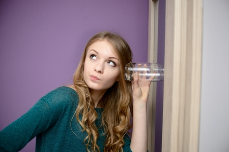 forbidden love: Young blonde woman listening in to a conversation with a glass pressed against her ear Stock Photo