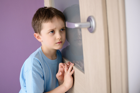 divorcio: Triste, asustado niño escuchando a un padre que habla a través de la puerta con un vidrio prensado a la oreja.