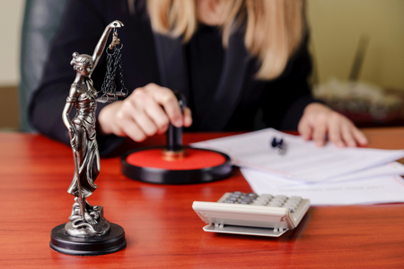 signing authority: The statue of Themis on the background of a working woman - notary public Stock Photo