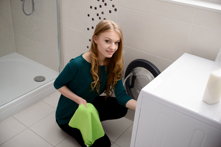 dirty blond: Young blond woman puts dirty laundry into the washing machine Stock Photo