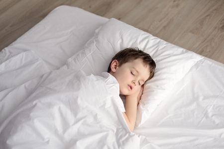 Tired little boy sleeping in bed, happy bedtime in white bedroom. Sleeping boy. Sleeping child