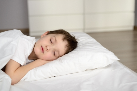morning night: Tired kid sleeping in bed, happy bedtime in white bedroom. Sleeping boy. Sleeping child