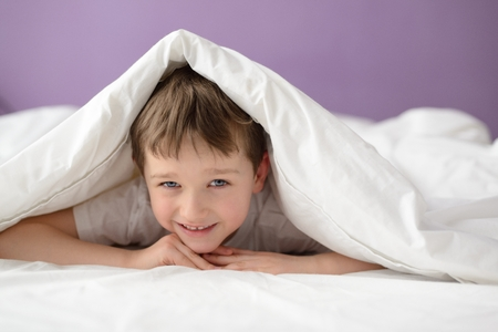 coverlet: Smiling boy hiding in bed under a white blanket or coverlet. Boy at bed. Child in bed