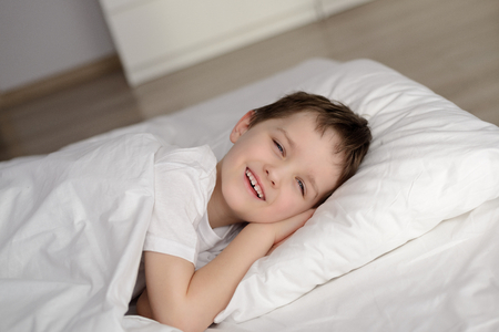 eyes open: Little boy waking up in white bed with eyes open. Sleeping boy. Sleeping child Stock Photo