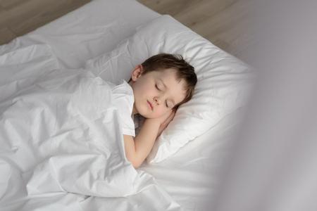 Entzückender Junge im Bett schlafen, glücklich Schlafenszeit in weißen Schlafzimmer. Schlafender Junge. Schlafendes Kind