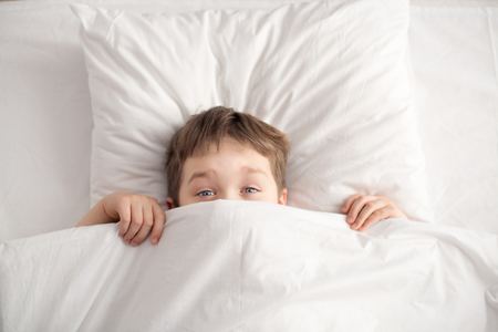 Cheerful boy in white bed under white blanket. Sleeping boy. Sleeping child