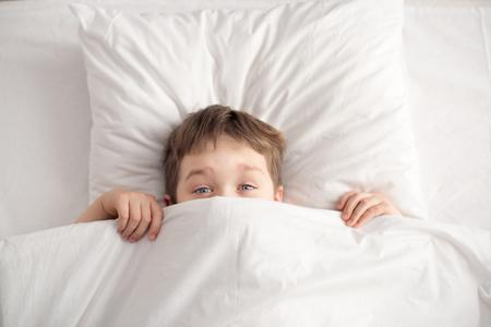 coverlet: Cheerful boy in white bed under white blanket. Sleeping boy. Sleeping child
