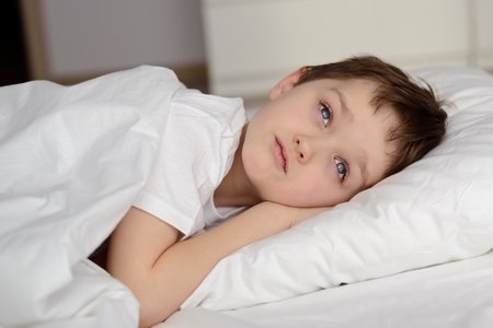 eyes open: 7 years old boy resting in white bed with eyes open. Sleeping boy. Sleeping child Stock Photo