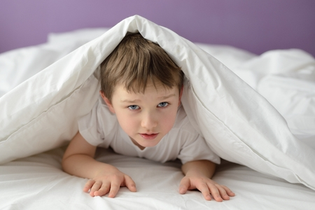 coverlet: 7 years old boy hiding in bed under a white blanket or coverlet. Boy at bed. Child in bed Stock Photo