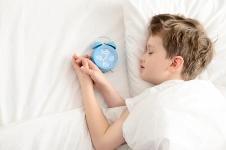 dia y noche: Vista superior del ni�o peque�o que duerme en la cama blanca con el reloj de alarma cerca de su cabeza. Durmiente. Ni�o durmiendo