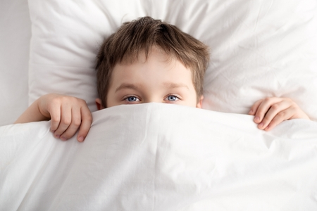 coverlet: Top view of little boy in bed covering his face with white blanket or coverlet. Sleeping boy. Sleeping child Stock Photo