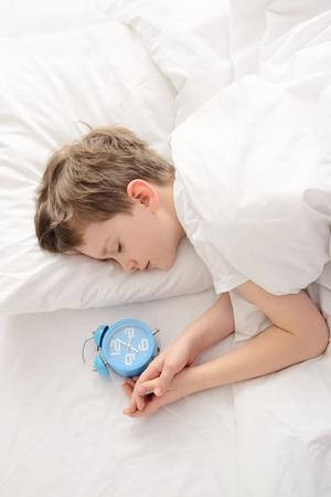 Draufsicht des kleinen Jungen mit Wecker in der Nähe von seinem Kopf zu schlafen. Schlafender Junge. Schlafendes Kind