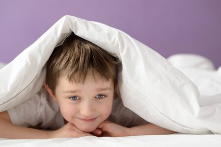 coverlet: Happy boy playing in bed under a white blanket or coverlet. Boy at bed. Child in bed Stock Photo