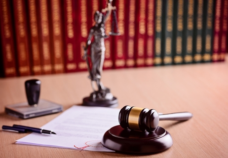 The composition of the gavel and judgement, statuette of goddess of justice Themis - with scales of justice, legal codes, stamps and pen. Law concept