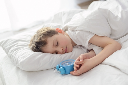 morning night: Little boy sleping in white bed with alarm clock near his head. Sleeping boy. Sleeping child Stock Photo
