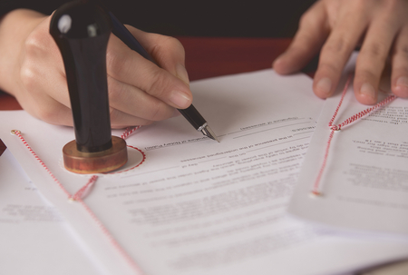 Close up on notaries public hand signing the testament and last will Stock Photo