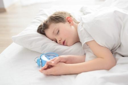 Kind schläft mit Wecker in der Nähe von seinem Kopf. Schlafender Junge. Schlafendes Kind