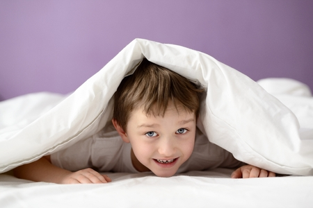 coverlet: Adorable laughing boy playing in bed under a white blanket or coverlet. Boy at bed. Child in bed