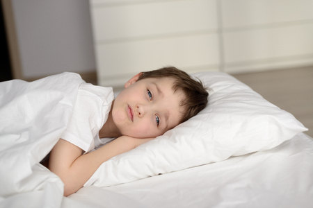 eyes open: Little schoolboy resting in white bed with eyes open. Sleeping boy. Sleeping child